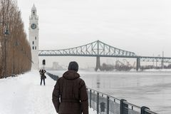St. Lawrence River with Clock tower in Old Montreal, in winter. Montreal, CA - 21 February 2019: St. Lawrence River, Clock tower and Jacques Cartier Bridge in royalty free stock photography