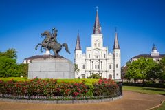 St. Louis Cathedral, Jackson Square, Louisiana, United States. Color horizontal image with Andrew Jackson statue in foreground with red flowers royalty free stock image