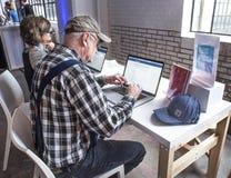 St Louis Missouri, den eniga Tillstånd-mars 27 2018-Old mannen, pensionären som använder datoren på Facebook gemenskap, ökar händ Arkivfoto