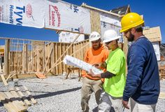 St. Louis, Missouri, United States-April 4, 2018-Three male construction workers, carpenters, wearing hardhats look at blueprints. Three male construction Royalty Free Stock Images