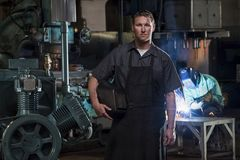 St Louis, Missouri, USA-circa 2015-Portrait of male welder with mask in manufacturing plant and man weld stock image