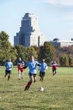 St. Louis, Missouri, Vereinigte Staaten - circa 2016 - Männer, die Fußball in Forest Park mit Verfolgungs-Park-Piazza-Hotel spiel stockfotografie