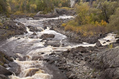 St. Louis River & Dam. After a dam, a river rushes through rocks in autumn Royalty Free Stock Image