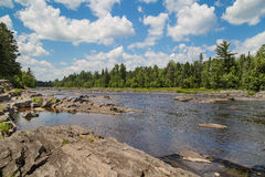 St. Louis River runs through a rocky streambed through a pine wo Stock Images