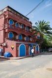 St Louis, Sénégal - 14 octobre 2013 : La maison coloniale colorée avec du vin rouge a peint des murs et des fenêtres et des porte photos stock