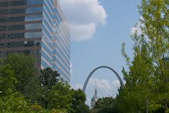 St. Louis Scene. A modern office building seen through the trees of a local park, with the St. Louis Arch and Capitol building in the distance Royalty Free Stock Images