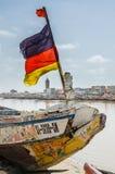 St Louis, Senegal - 12 de outubro de 2014: Barco de pesca ou pirogue de madeira pintado colorido com a bandeira alemão na costa Imagens de Stock