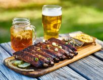 St louis style bbq ribs with collard greens and mac & cheese outside on picnic table during sunny summer day royalty free stock image