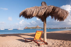 Sun Lounger and shade on Beach overlooking bay. Sun lounger and Sun shade on Redoute Beach St Lucia Stock Photo