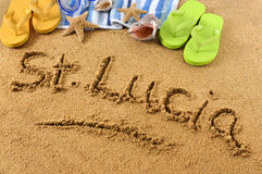 St Lucia beach sand word writing. The words St Lucia written on a sandy beach, with scuba mask, beach towel, starfish and flip flops Stock Image