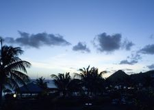 St. lucia sunset. St Lucia in the West Indies sunset on the caribbean at the Sandals Grande Resort with palm trees and ocean silhouette in Rodney Bay in the stock photo