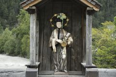 St. Lukas statue in wooden cottage on old bridge over Bad inn river. At Pfunds village in evening time in Tyrol, Austria Stock Images