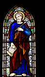 St Luke the Evangelist. Detail of victorian stained glass church window in Fringford depicting St Luke the Evangelist, a scroll in his hands with the beginning Stock Photos