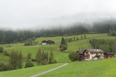 ST MAGDALENA ITALIEN - SEPTEMBER 14, 2015: Traditionella hus i en molnig mornig som omges av gräsplan, betar Arkivfoton