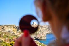 St Marija in Comino through an earring. Santa Marija Bay - or Saint Mary`s castle - on the Mediterranean Sea in Comino Island, Malta Royalty Free Stock Photography