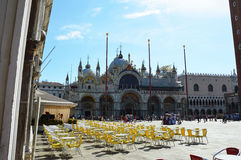 St Mark`s Square Venice with St Mark`s Basilica in sunny day, tables and chairs of a restaurant with tourists on the bottom, Venic Stock Image
