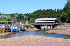 St. Martins, New Brunswick wharf. Fishing wharf in St. Martins, New Brunswick, Canada on low tide with moored boats in mud with a covered bridge in the Stock Images