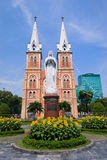 St Mary / Notre Dame Cathedral - Saigon - Vietnam. Sunflowers, blue sky, modern building behind Stock Photography