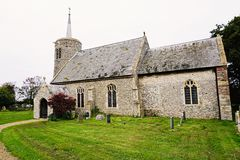 St Mary's Church. Dating from the 11th century Titchwell village church has a round tower and an individual spirelet with a substantial cross on top Stock Images