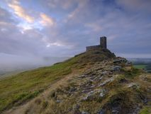 St Michael`s church atop Brentor, Devon, UK. Summer sunrise on Brentor showing St Michael`s church atop the tor with dramatic weather clouds of showers and mist royalty free stock images