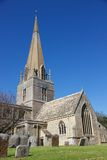 St. Michael's Church in Bampton Village, England, United Kingdom. A view of the ancient stone St. Michael's Church in Bampton Village, England, with gravestones Stock Photo