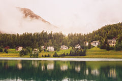St. Moritz mountain lake in summer Grisons, Switzerland. Reflections in the St. Moritz mountain lake on a heavily clouded day in summer. Engadin, Grisons Stock Image