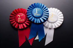 1st, 2nd and 3rd place pleated ribbon rosettes. 1st, 2nd and 3rd place pleated ribbon rosette on a dark background Stock Images