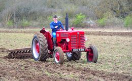 Vintage red International 1960`s  tractor ploughing field. ST NEOTS, CAMBRIDGESHIRE, ENGLAND - MARCH 19, 2017: Vintage red International 1960`s  tractor Stock Image