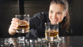 St?ng- och coctailbegrepp Kvinnlig bartender i svart likformig som ler på kameran, medan göra coctailar Utelivbegrepp arkivfilmer