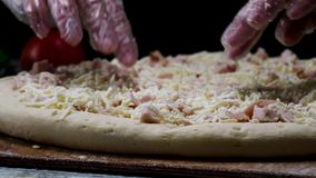 St?ng sig upp f?r kockh?nder i genomskinliga handskar som trycker p? unbaked pizza p? svart bakgrund och att laga mat begrepp Ram arkivfilmer