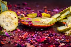 St?ng upp av Ayurvedic ansiktsmasks ingredienser I e-gurkan och aloe Vera stelnar med rosa kronblad p? en tr?yttersida i m?rkt go arkivbild