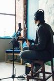 St?ng upp av en mans?ngare att sitta p? en stol i h?rlurar med en gitarr som antecknar ett sp?r i en hem- studio fotografering för bildbyråer