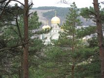 St. Nicholas Cathedral in Kislovodsk. Its Golden domes are visible among the pines. In the foreground high pine trees, and in the distance against the green royalty free stock images