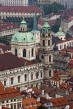 ST Nicholas Church και οι κόκκινες στέγες στην Πράγα Στοκ Φωτογραφία