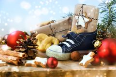 St. Nicholas Day, Children`s shoe with sweets, gifts and christm. As ornaments on rustic wood, light blue snowy background, in Germany called Nikolaus, selected royalty free stock photos