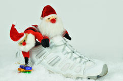 St Nicholas`Day. Two Santa Claus with sweets inside a white sports shoe on white, snowy background, close up, horizontal Royalty Free Stock Images