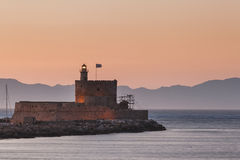 St. Nicholas Fortress and lighthouse at sunset. Rhodes Island. Greece Royalty Free Stock Photo