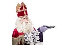 St Nicholas hållande fjärrkontroll på vit bakgrund arkivbilder