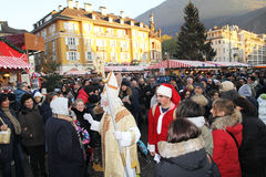 St nicholas. A saint nicholas is walking with elfs in the christmas market of bolzano in italy Royalty Free Stock Photo