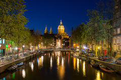 St.Nicolas church and canals at night in Amsterdam, Netherlands. Royalty Free Stock Photography