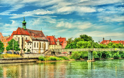 St. Oswald Church with Eiserner Steg bridge across the Danube River in Regensburg, Germany Royalty Free Stock Images