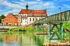 St Oswald Church met de brug van Eiserner Steg over de Rivier van Donau in Regensburg, Duitsland stock foto