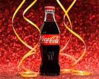 St PÉTERSBOURG, RUSSIE - 8 DÉCEMBRE 2014 : Bouteille classique de Coca-Cola sur le fond rouge de scintillement Images libres de droits