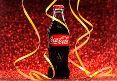 St PÉTERSBOURG, RUSSIE - 8 DÉCEMBRE 2014 : Bouteille classique de Coca-Cola sur le fond rouge de scintillement Image stock