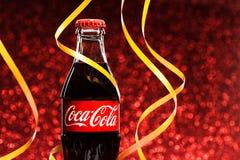 St PÉTERSBOURG, RUSSIE - 8 DÉCEMBRE 2014 : Bouteille classique de Coca-Cola sur le fond rouge de scintillement Photos libres de droits