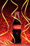 St PÉTERSBOURG, RUSSIE - 8 DÉCEMBRE 2014 : Bouteille classique de Coca-Cola sur le fond rouge de scintillement Photographie stock