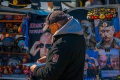 St PÉTERSBOURG, RUSSIE, LE 1ER MAI 2018 : Homme non identifié recherchant des souvenirs en tant que poupées russes de babushka de Images stock