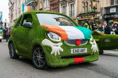 St Patrick`s Parade in London. 18 March 2018 - London, England. Very nice, unique and small Smart Brabus car, covered in artificial grass and Irish flag on the Stock Image
