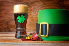 St.Patrick concept with green leprechaun hat, beer and gold. St. Patrick day concept with beer glass decorated green clover leaf, leprechaun hat and gold prill Royalty Free Stock Photo