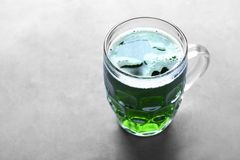 St. Patrick Day concept. Glass of green beer. On grey table royalty free stock photo